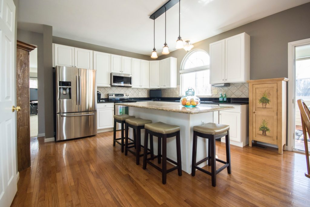 Modern kitchen with wood floors, stainless steel appliances, and white cabinets surrounding an island with a marble countertop