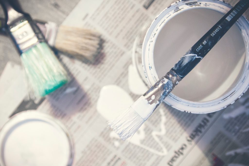 close-up of paint brush on top of white paint can sitting on newspaper