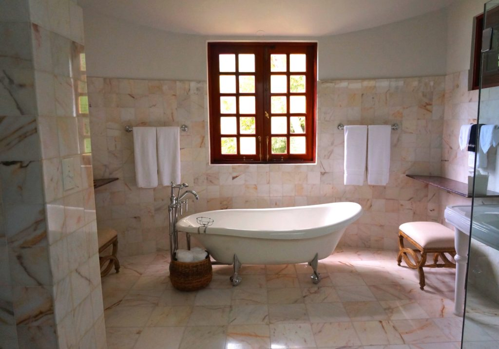 clawfoot bathtub in front of red, vintage window in bathroom with marbled tile covering floor and walls
