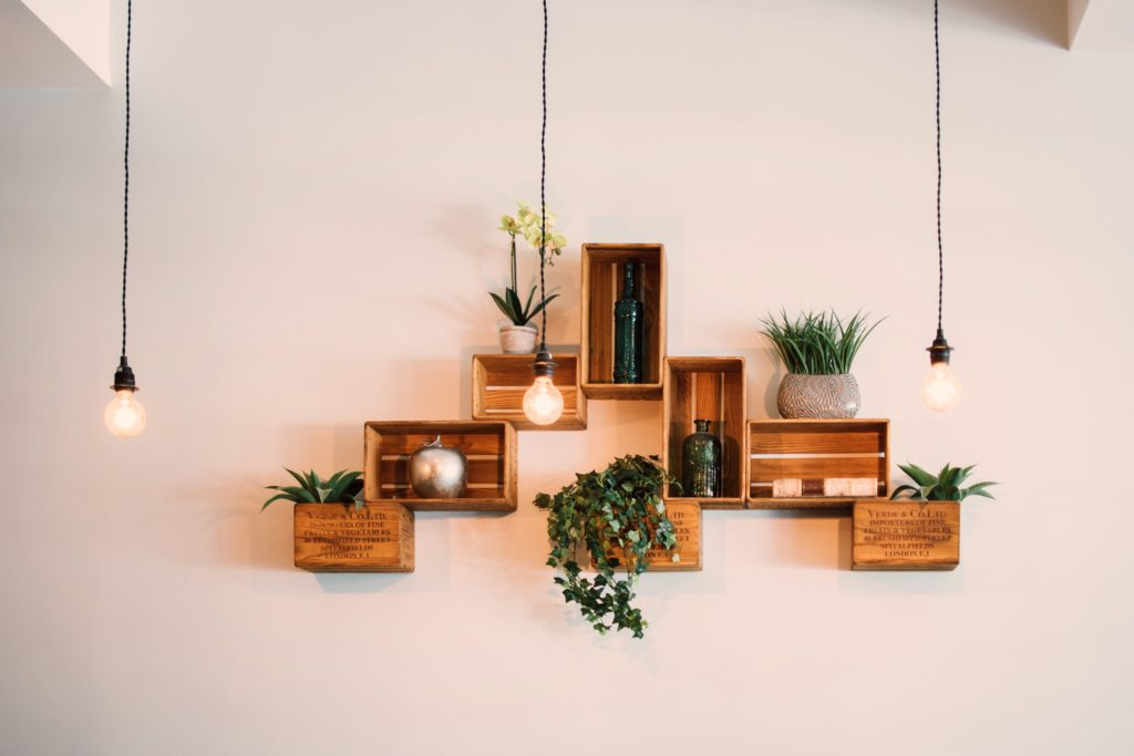 hanging light bulbs in front of wooden boxes holding plants on white wall